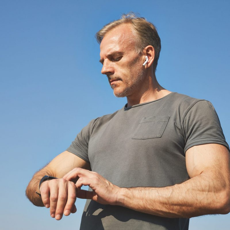 Confident handsome mature man in ear buds standing against blue sky and taking pulse with smartwatch